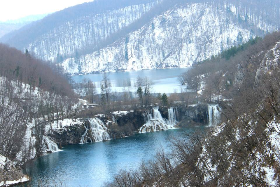 winter wanderland at plitvice lakes with mountains covered in snow, frozen waterfalls and fronzen lake