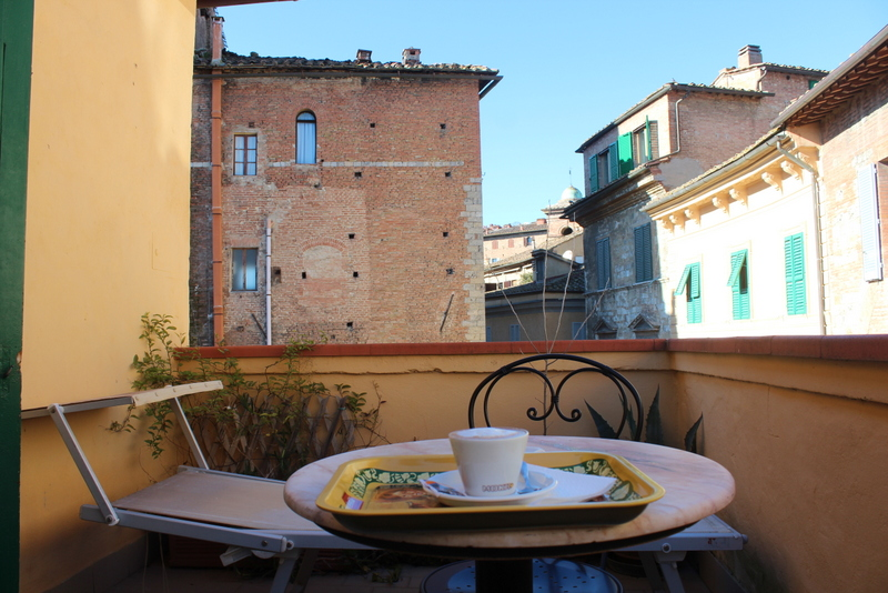 balcony with a chair, a cappuccino on the table, surrounded by pastel typical italian buildings in siena
