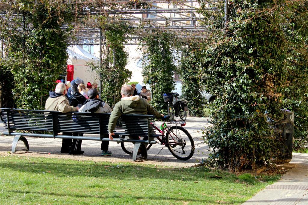 three elderly locals sitting on a bench in a park in pisa