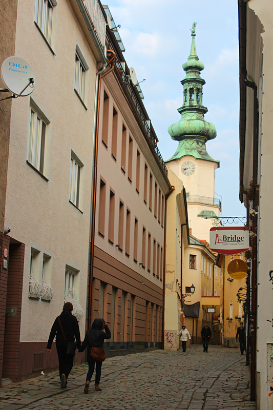two locals walking in a street of the old town of bratislava