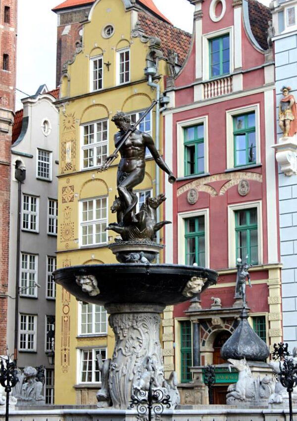 statue in the main square of gdansk, surrounded by colorful buildings