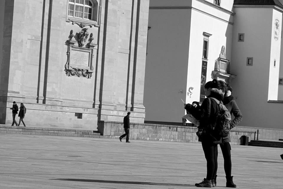 tourist girls looking at the map of Vilnius city